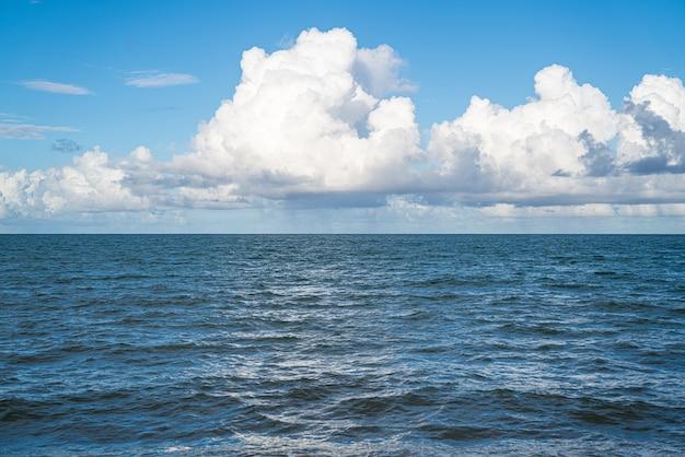 Fond bleu marin naturel d'été apaisant. mer et ciel avec nuages blancs