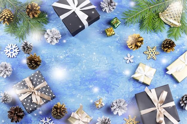 Fond bleu de noël avec des branches de sapin, des coffrets cadeaux, des décorations argentées et dorées, espace de copie. vue de dessus