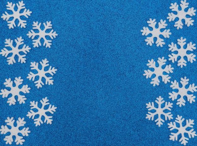 Fond bleu de noël ou d'hiver avec des flocons de neige blancs. carte de voeux de nouvel an.