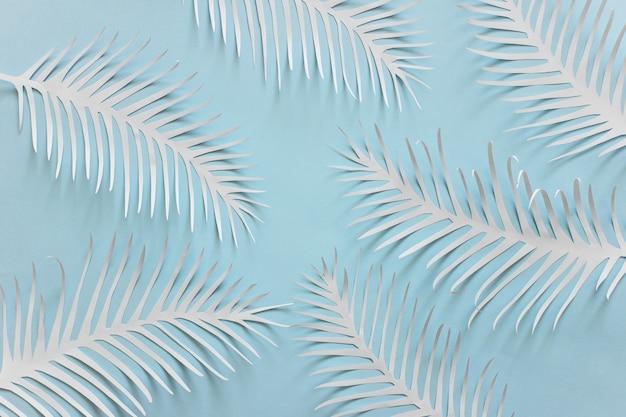 Fond bleu avec des plumes de papier blanc épineux