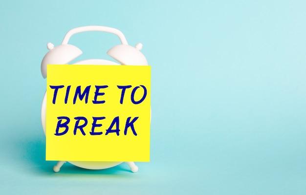 Sur fond bleu - un réveil blanc avec un autocollant jaune pour les notes avec le texte time to break.