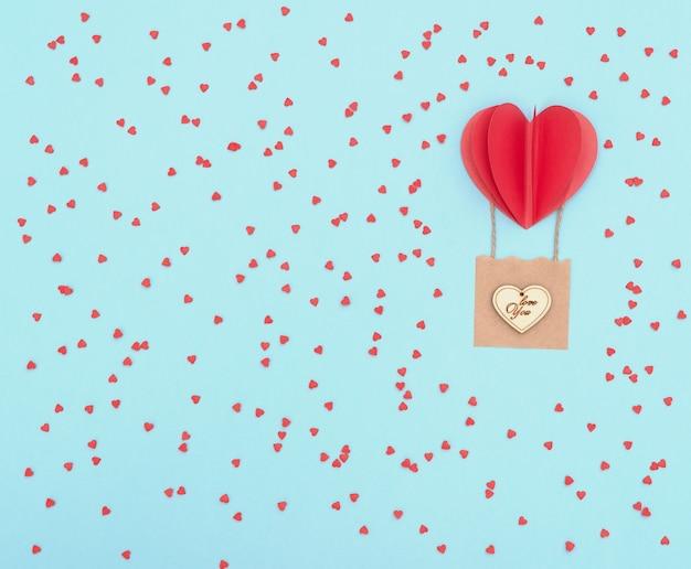 Fond bleu de la saint-valentin avec ballon coeur rouge avec panier avec coeur en bois dessus et beaucoup de coeurs rouges