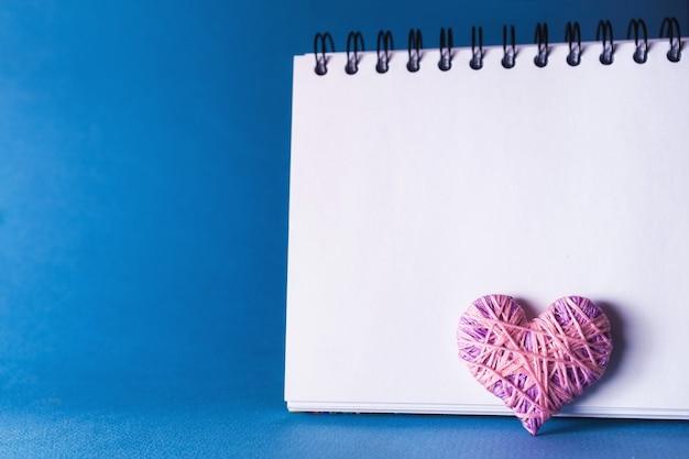 Fond bleu simple avec un petit cahier yn coeur rouge violet. place pour le texte