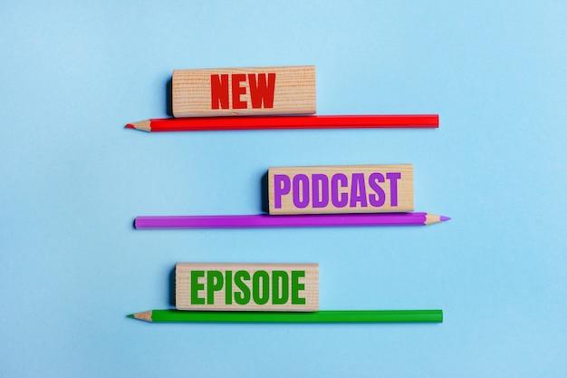 Sur fond bleu, trois crayons de couleur, trois blocs de bois avec texte new podcast episode