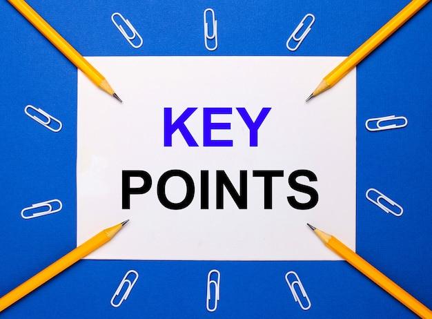 Sur un fond bleu, des trombones blancs, des crayons jaunes et une feuille de papier blanche avec le texte points clés