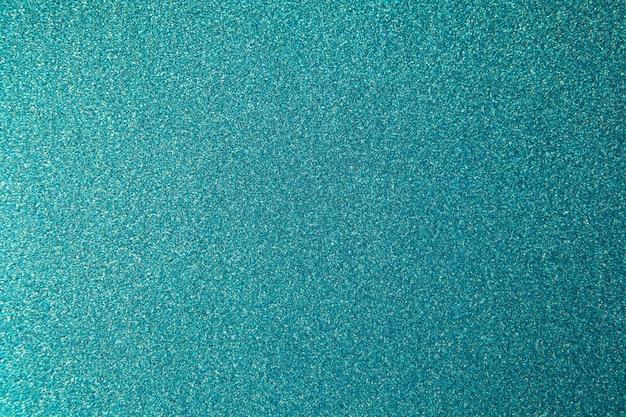 Fond bleu-vert de paillettes métalliques, texture avec espace de copie.