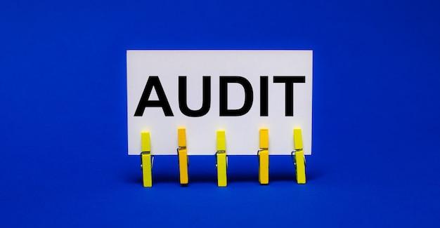 Sur un fond bleu vif sur des pinces à linge jaunes, une carte blanche avec le texte audit