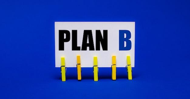 Sur un fond bleu vif sur des pinces à linge jaunes, une carte blanche avec le texte plan b
