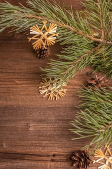 Fond en bois ancien festif de noël. concept de décoration de noël zéro déchet. branches de pin à feuilles persistantes fraîches et flocons de neige en paille, pose à plat