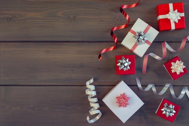 Sur un fond en bois, beaucoup de boîtes-cadeaux rouges et blancs.