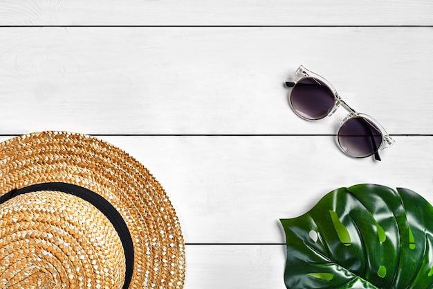 Fond en bois blanc avec chapeau de paille, lunettes de soleil et feuille verte