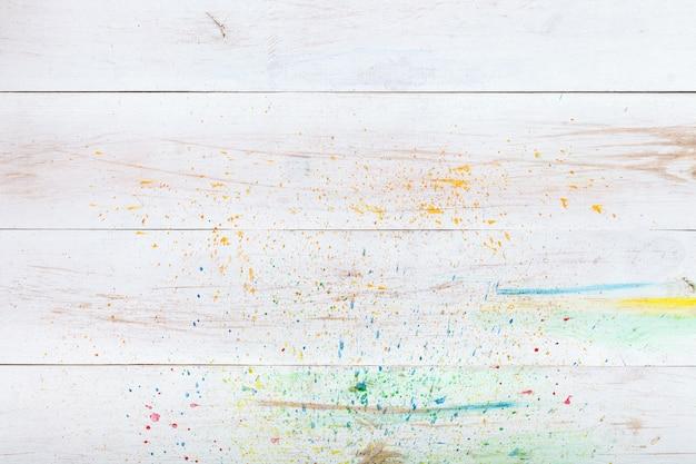 Fond en bois blanc avec des éclaboussures de peinture, vue de dessus d'en haut, copie espace