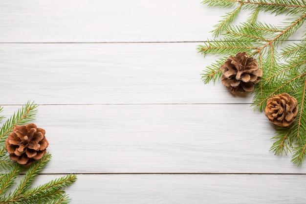 Fond en bois blanc de noël avec des branches de sapin et des cônes
