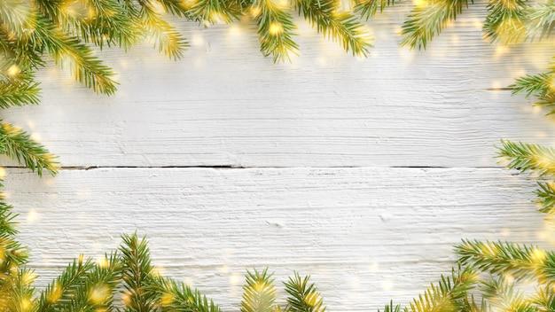 Fond en bois blanc de noël et du nouvel an avec des branches de sapin et des lumières dorées rougeoyantes. cadre ou bordure de noël