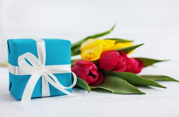 Fond en bois blanc, tulipes et cadeau bleu.