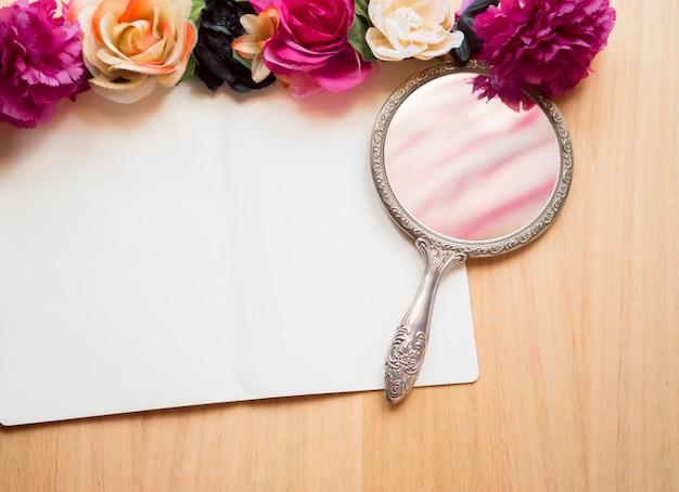 Fond en bois, bloc-notes blanc, fleurs et miroir