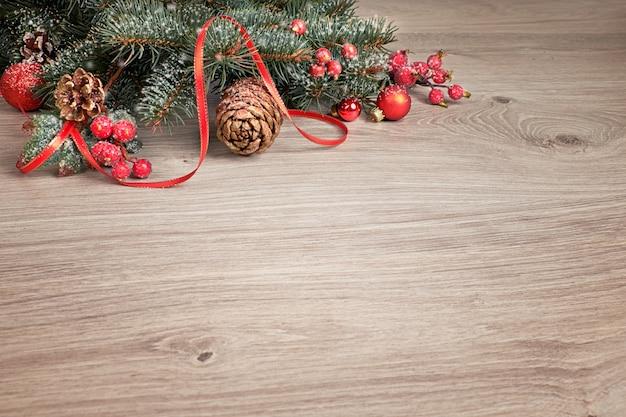 Fond en bois avec des brindilles d'arbre de noël décorées