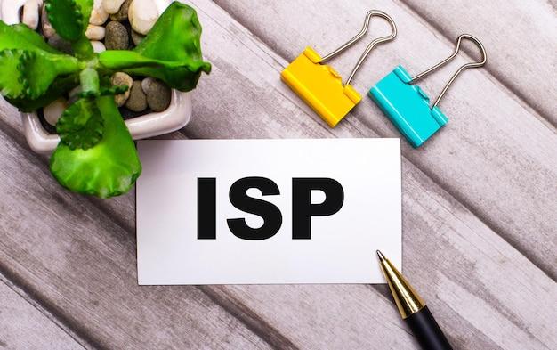 Sur un fond en bois, une carte blanche avec le texte isp internet service provider, des trombones jaunes et verts et une plante dans un pot. vue d'en-haut