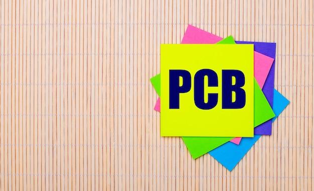 Sur un fond en bois clair, autocollants multicolores lumineux avec le texte pcb printed circuit board
