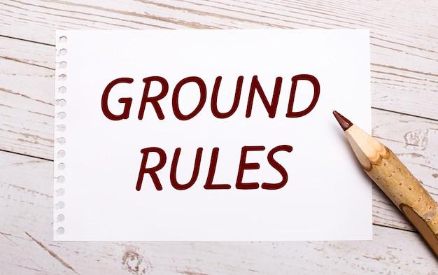 Sur un fond en bois clair, un crayon de couleur et une feuille de papier blanc avec le texte règles de base