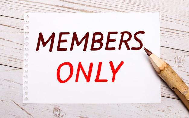 Sur un fond en bois clair, un crayon de couleur et une feuille de papier blanche avec le texte membres only