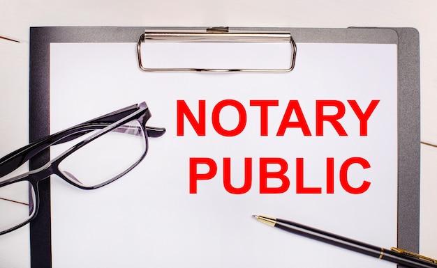Sur un fond en bois clair des lunettes, un stylo et une feuille de papier avec le texte notaire public. concept d'entreprise