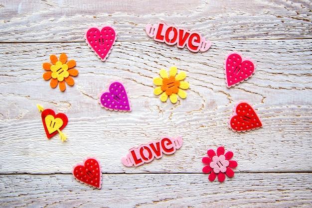 Fond en bois avec des coeurs, des fleurs et le mot love le jour de la saint-valentin