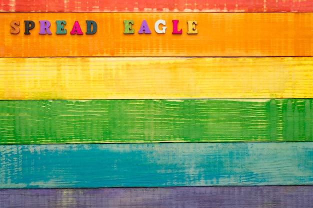 Fond en bois de couleurs arc-en-ciel lgbt, avec inscription aigle répandu dans le coin supérieur gauche, espace copie, mise à plat, vue de dessus