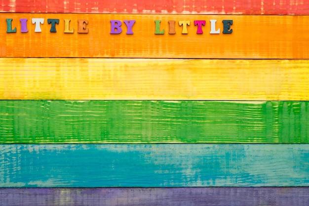 Fond en bois de couleurs arc-en-ciel lgbt, avec inscription petit à petit dans le coin supérieur gauche, espace copie, mise à plat, vue de dessus