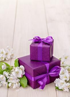 Sur fond de bois, deux boîtes avec des cadeaux dans un emballage violet.
