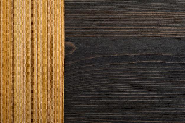 Fond en bois foncé avec serviette jaune