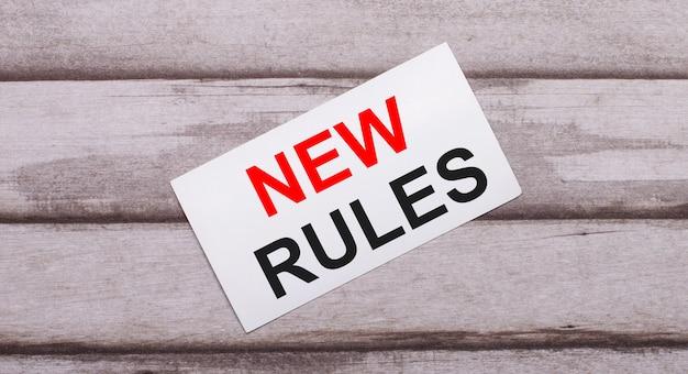 Sur un fond en bois, il y a une carte blanche avec du texte rouge nouvelles règles