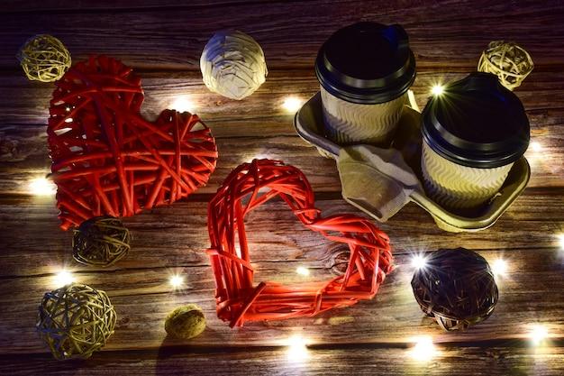 Sur un fond en bois, il y a deux tasses de café à droite et deux grands cœurs tressés décoratifs à gauche. les lumières rougeoyantes sont dispersées autour