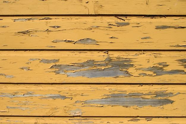 Fond en bois jaune avec des morceaux de peinture ancienne pelés.