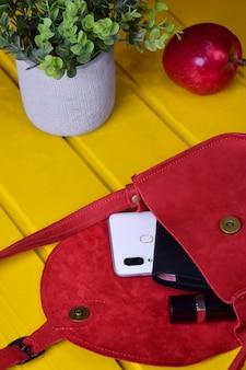 Sur un fond en bois jaune, un sac à main en cuir rouge pour femme est ouvert, un portefeuille, un téléphone portable et un rouge à lèvres en sortent. en arrière-plan une pomme et un pot de fleurs
