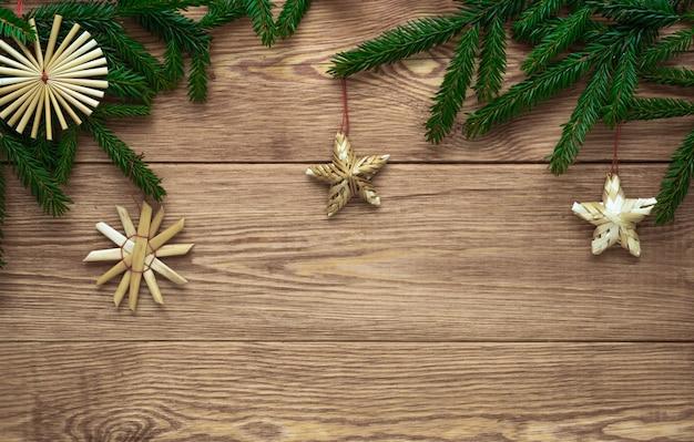 Fond en bois de noël avec des branches de décorations d'arbre de noël et de paille, espace vide, concept de noël et du nouvel an, style rustique