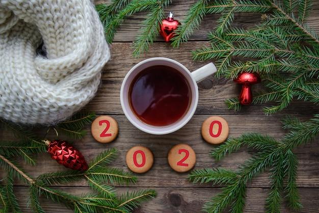 Fond en bois de noël avec une tasse de thé, des biscuits, des écharpes pour le nouvel an 2020