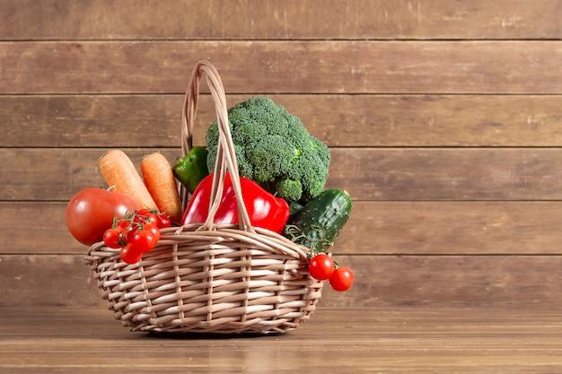 Fond en bois avec un panier plein de légumes