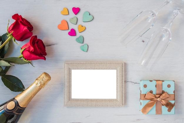 Fond en bois avec roses, coeurs, verres de champagne, champagne, cadre photo, espace copie