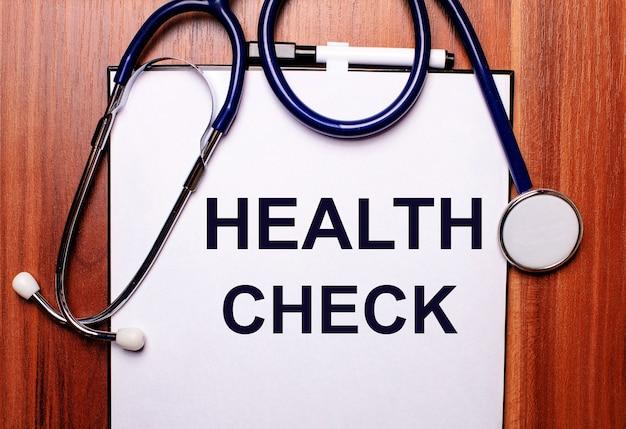 Sur un fond en bois se trouve un stéthoscope et une feuille de papier avec l'inscription health check