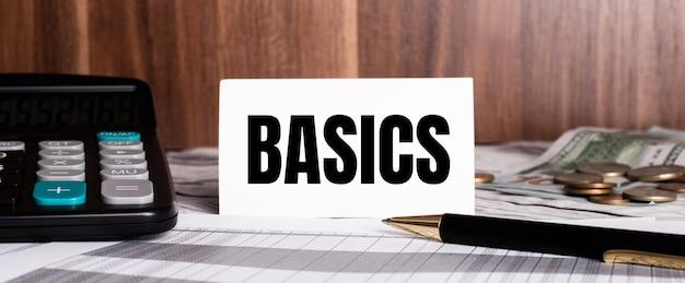 Sur un fond en bois se trouve un stylo avec une calculatrice et une carte blanche avec le mot basics
