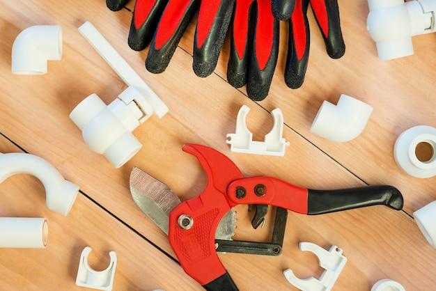 Sur un fond en bois se trouvent des outils pour réparer les tuyaux en plastique.
