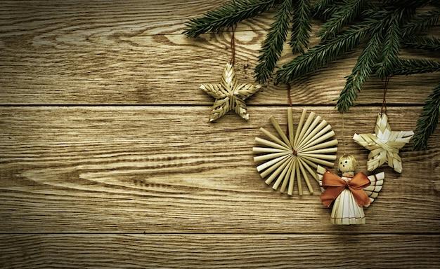 Fond en bois vintage de noël avec des branches de sapin et décorations de paille