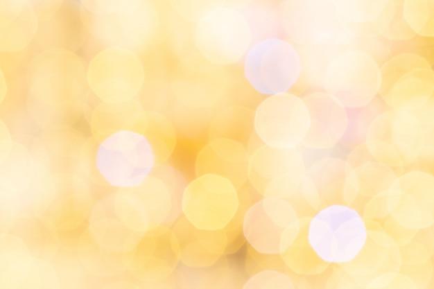 Fond de bokeh doré. lumières de flou festif abstrait paillettes. décor de noël jaune doux.