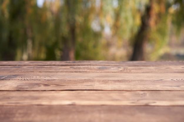 Fond de bokeh nature table en bois vide avec un thème de plein air de pays, modèle maquette pour l'affichage de l'espace de copie de produit