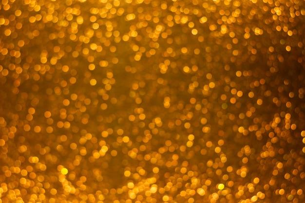 Fond de bokeh or brillant de vacances, paillettes, scintille, lueur défocalisé