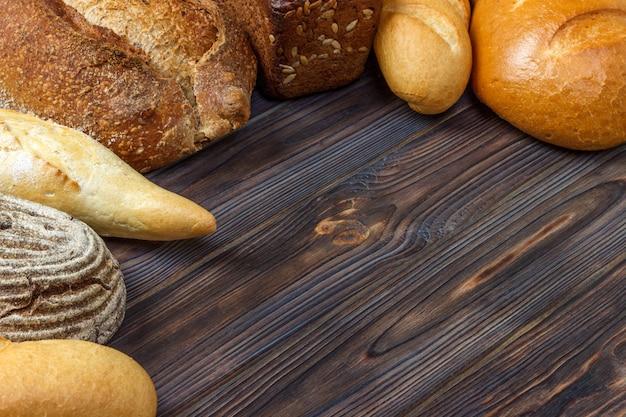 Fond de boulangerie, assortiment de pain sur fond en bois noir