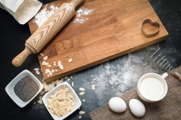 Fond de boulangerie. ingrédients de cuisson sains - farine, noix d'amande, œufs, lait sur fond noir. vue de dessus, espace de copie, mise à plat. composition de cuisine moderne. ustensiles de cuisine.