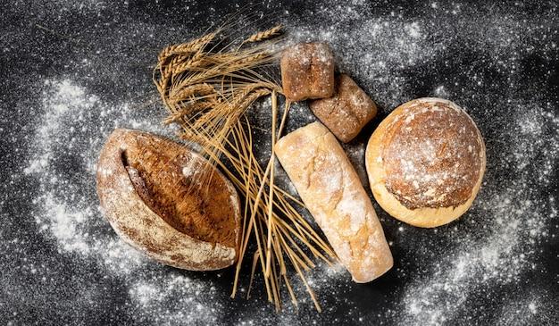 Fond de boulangerie. pain et petits pains croustillants fraîchement sortis du four avec vue de dessus d'épis de blé