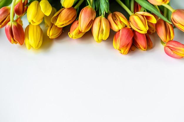 Fond Avec Un Bouquet De Tulipes Jaunes, Orange Et Rouges. Vue De Dessus. Espace Copie Photo Premium